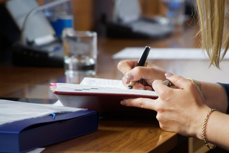 H?nder av en ung kvinna som skriver anm?rkningar i en dagbok arkivbild