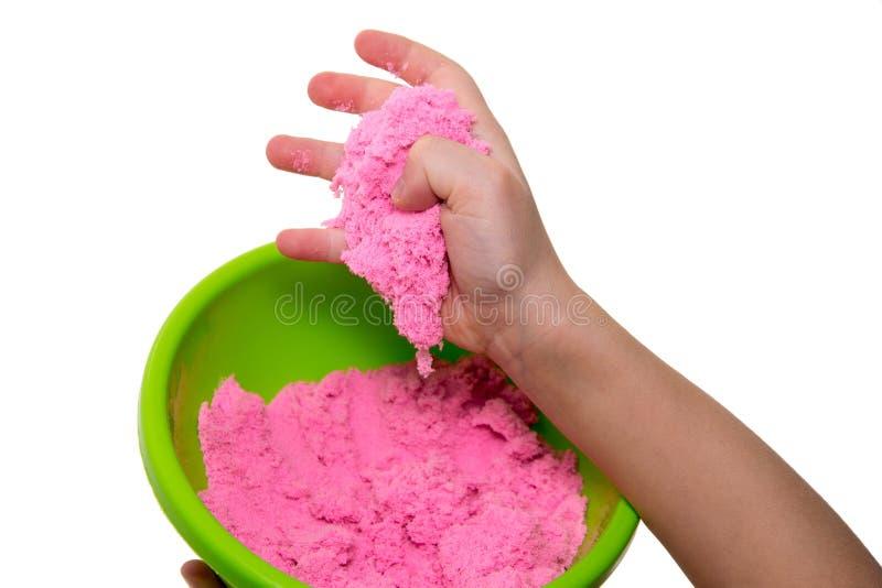 Händer av en unge som spelar med rosa magisk sand royaltyfri foto