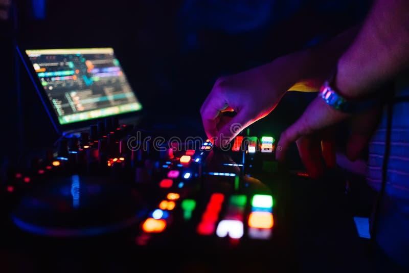 Händer av en yrkesmässig discjockey som spelar och blandar musik för ett slummerparti royaltyfri foto