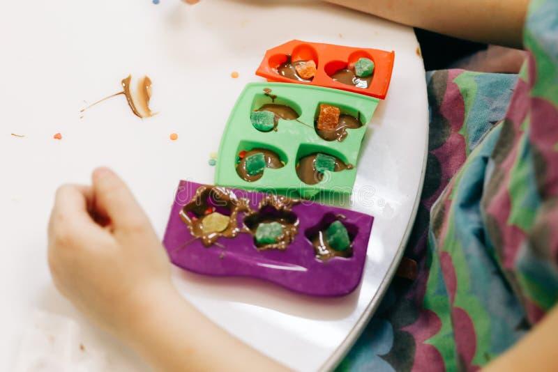 Händer av ett barn, en mästarklass, i att laga mat choklad, vikande, frukt och choklad in i former arkivbilder
