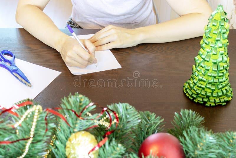 Händer av ett kvinnasammanträde vid tabell- och handstiljulönskaen på ett kort, bokstav arkivfoton