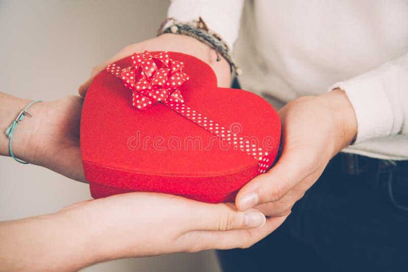 Händer av ett par som rymmer en röd hjärta, formade gåvaasken arkivbild