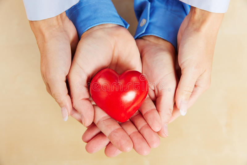 Händer av ett par som rymmer röd hjärta arkivfoto