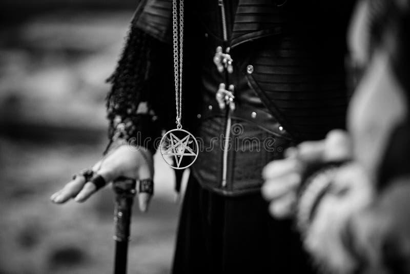 Händer av ett psykiskt med en rotting och en pentagram runt om hans hals i processen av ritualen royaltyfri bild
