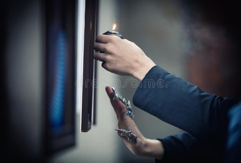 Händer av ett psykiskt med en stearinljus i processen av ritualen royaltyfria foton