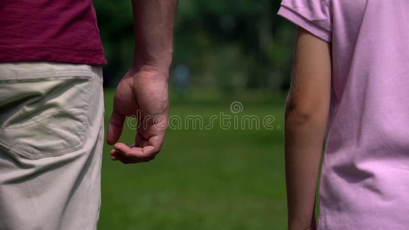 Händer av farsan och sonen ifrån varandra, skilsmässainverkan på barn, brist av mäns uppfostran arkivfoto
