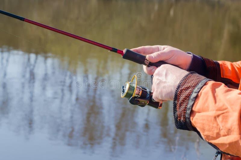 Händer av fiskaren med snurr royaltyfri fotografi