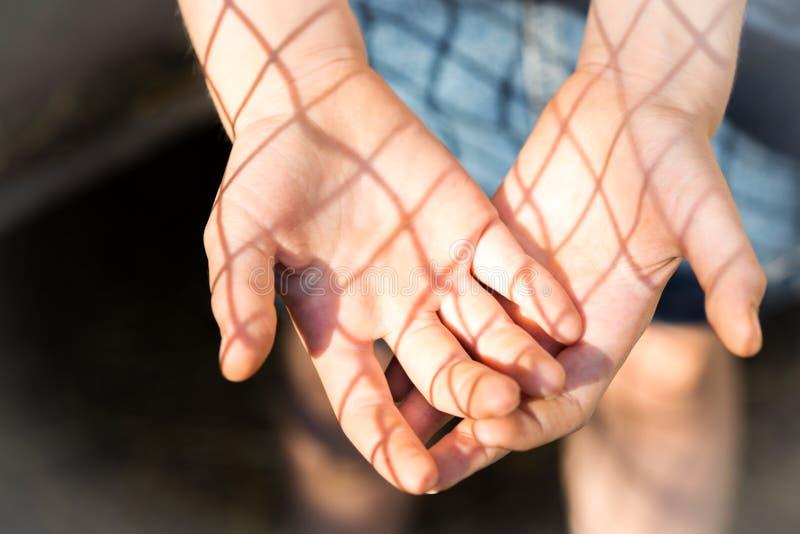 Händer av flickan och skuggan från spisgallret arkivbild