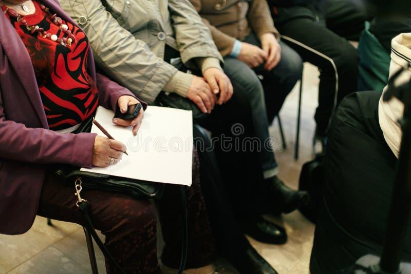 Händer av folk som rymmer anmärkningar och lär och skriver på businen arkivfoto