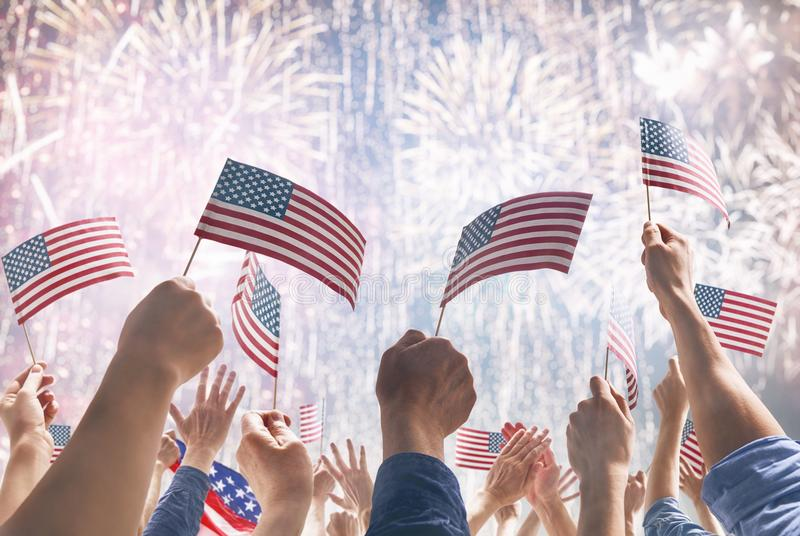 Händer av folk som rymmer flaggorna av USA royaltyfria bilder