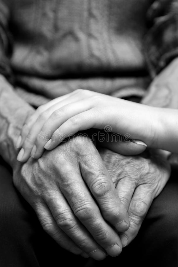 Händer av gamala mannen och en ung kvinna royaltyfria bilder