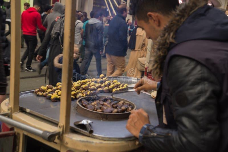 Händer av gatuförsäljarekastanjer Grillade kastanjer i gatuförsäljare Populär mat bland turister och turker Istanbul Turkiet arkivbild