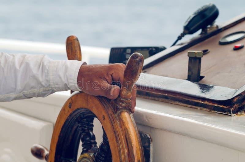 Händer av kaptenen som rymmer hjulet på däcket av skeppet arkivbilder