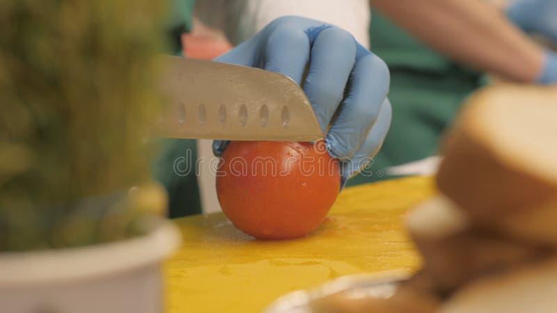 Händer av kocken som använder kniven för bitande tomat på cirkelskivor och stycken i restaurang royaltyfria bilder
