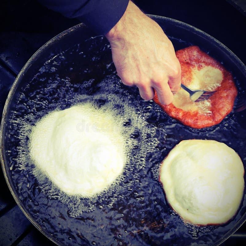 Händer av kocken som steker stor frybread i en panna av varm olja royaltyfri fotografi
