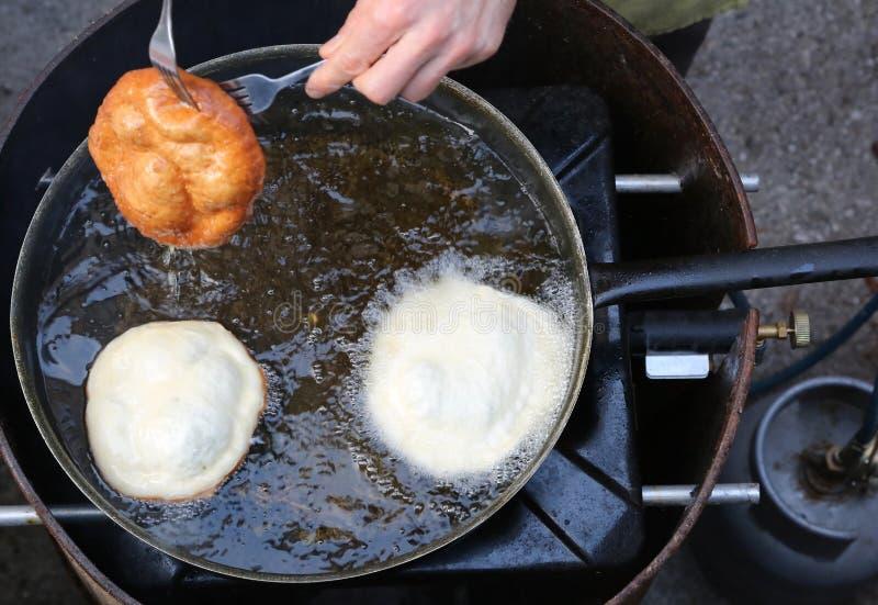Händer av kocken som steker stora pannkakor i en panna av varm olja i en stree arkivbilder