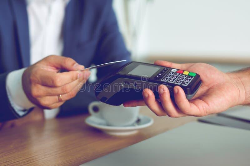 Händer av kunden som betalar restaurangen, fakturerar genom att använda kreditkorten royaltyfria foton