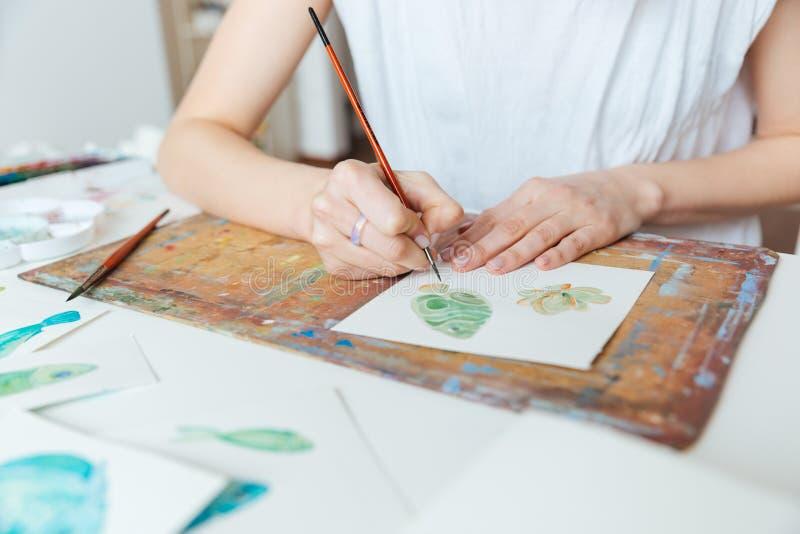 Händer av kvinnakonstnärmålning med målarpensel- och vattenfärgmålarfärger arkivbilder