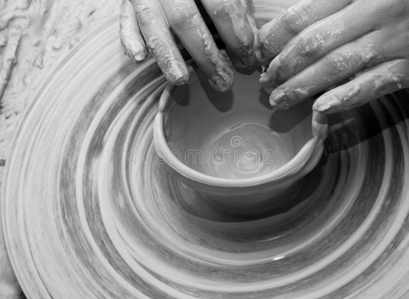 Händer av kvinnan i process av att göra lerabunken på krukmakerihjulet arkivfoton
