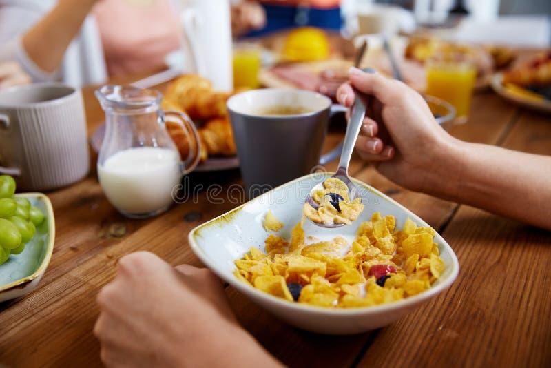 Händer av kvinnan som äter sädesslag för frukost fotografering för bildbyråer