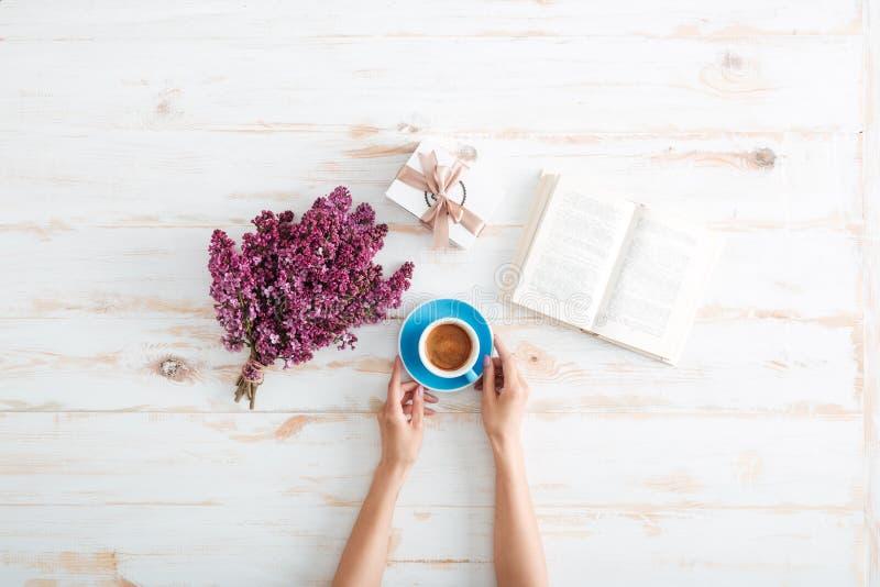 Händer av kvinnan som dricker kaffe och läseboken på tabellen arkivfoto