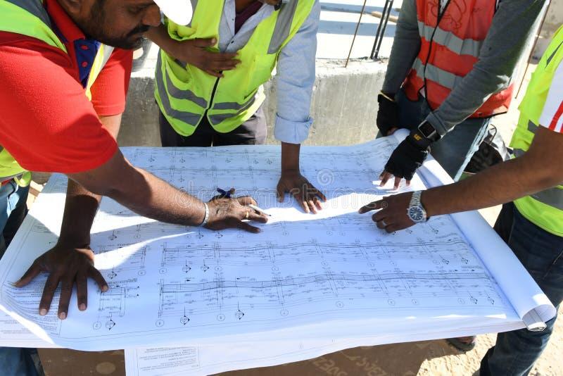 Händer av män som visar ritningarna på konstruktionsplatsen royaltyfri foto