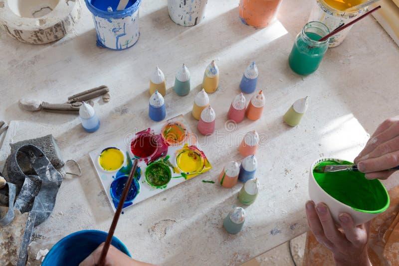 Händer av manlig keramiker- och flickamålning bowlar arkivbild