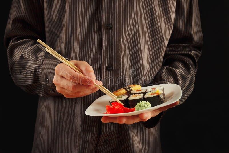 Händer av mannen i en svart skjorta rymmer en platta med sushi på svart bakgrund arkivbild