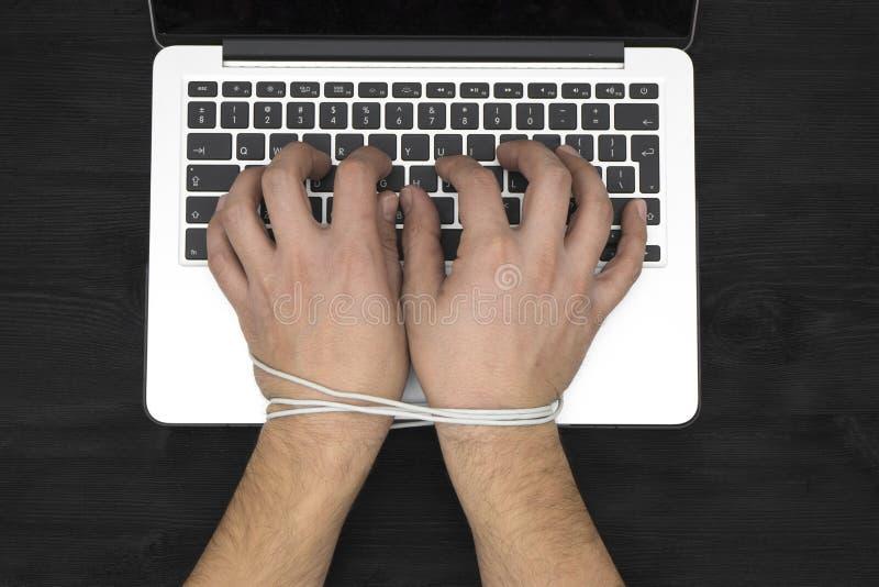 Händer av mannen missbrukade till datoren, internetslav arkivbilder