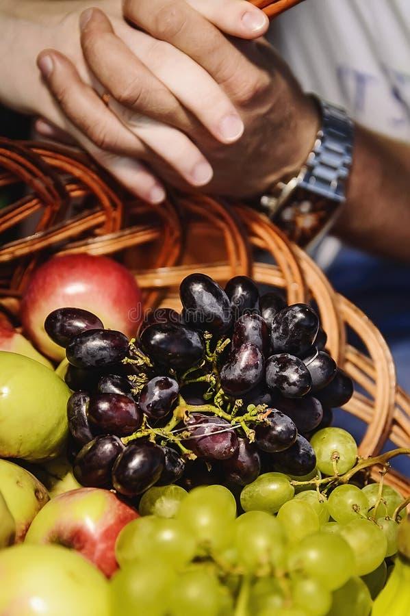 Händer av mannen och kvinnan på en korg av frukt arkivfoton