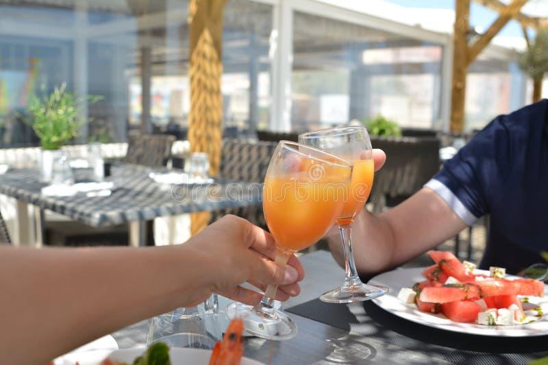 Händer av mannen och kvinnor med exponeringsglas av fruktsaft i händerna i en restaurang royaltyfri foto