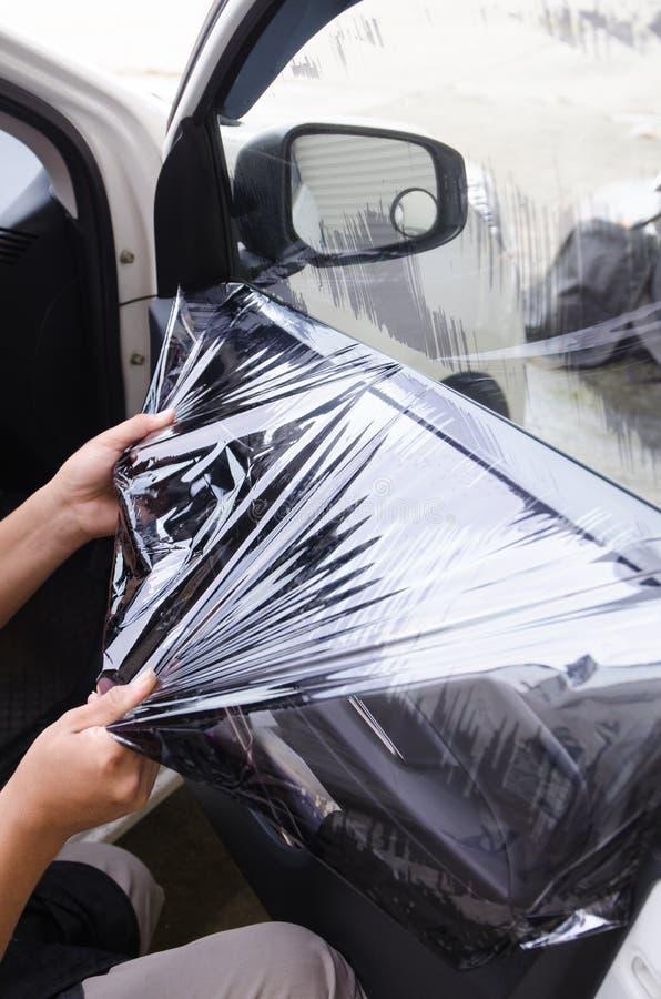 Händer av mannen som tar bort den gamla filmen för bilfönster royaltyfria bilder