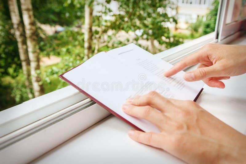 Händer av närbilden för flickapunktbok arkivfoton