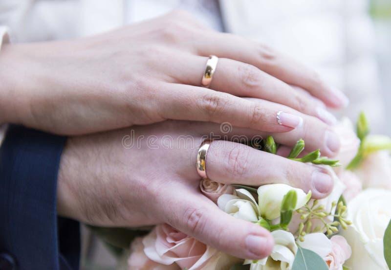 Händer av nygifta personer med att gifta sig guld- cirklar på den gifta sig buketten arkivbilder
