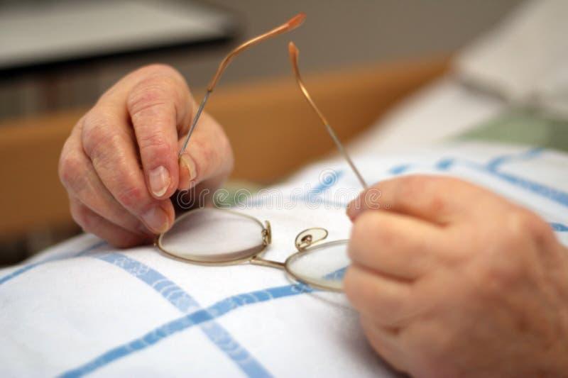 Händer av omsorg-beroende exponeringsglas för en personholding arkivfoto