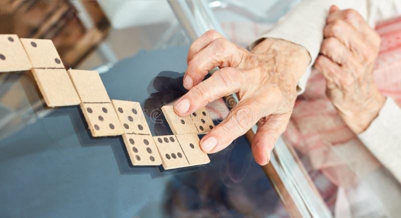 Händer av pensionärer lägger räknare på dominobrickan arkivfoton