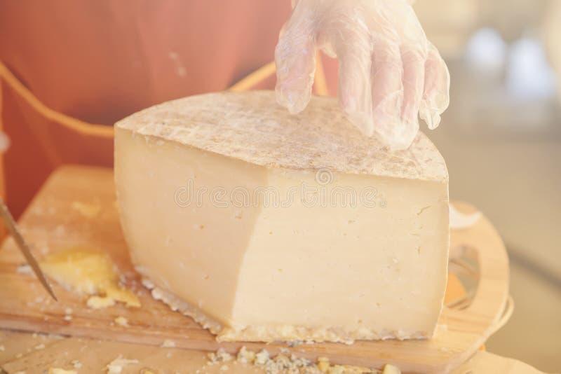 Händer av säljaren i handskar och halvan av ett stort huvud av ostnärbilden, träbräde Selektivt fokusera Gastronomiskt mejeri royaltyfri bild