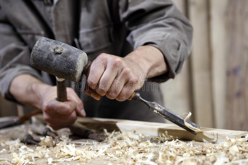 Händer av snickaren med en hammare och en stämjärn på arbetsbänken i snickeri arkivfoton