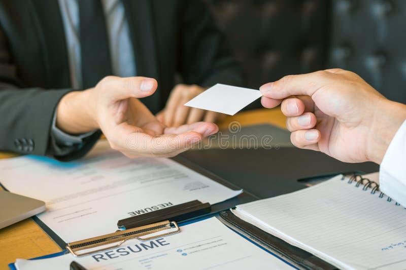 Händer av två affärspersoner som i regeringsställning sitter rum som ger och tar det tomma affärskortet arkivfoton