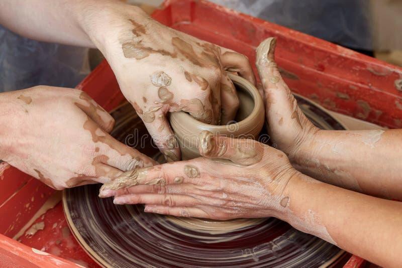 Händer av två personer skapar krukan, hjul för keramiker` s Undervisningkrukmakeri royaltyfri foto