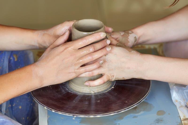 Händer av två personer skapar krukan, hjul för keramiker` s Undervisningkrukmakeri royaltyfria bilder