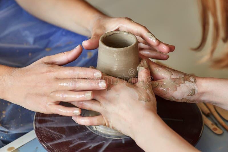 Händer av två personer skapar krukan, hjul för keramiker` s Undervisningkrukmakeri royaltyfri fotografi