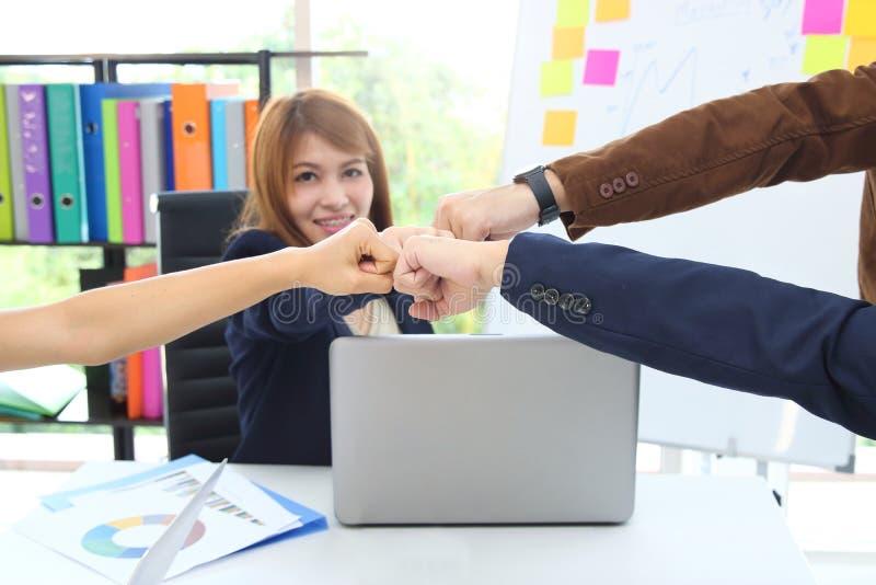 Händer av ungt affärsfolk som ger näven, knuffar till tillsammans till att hälsa färdigt handla i regeringsställning Framgång- oc arkivbilder