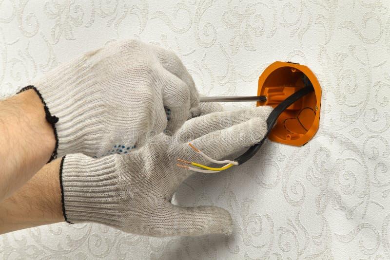 Händer fäster hålighetasken till väggen för att förlägga det elektriska uttaget royaltyfri foto