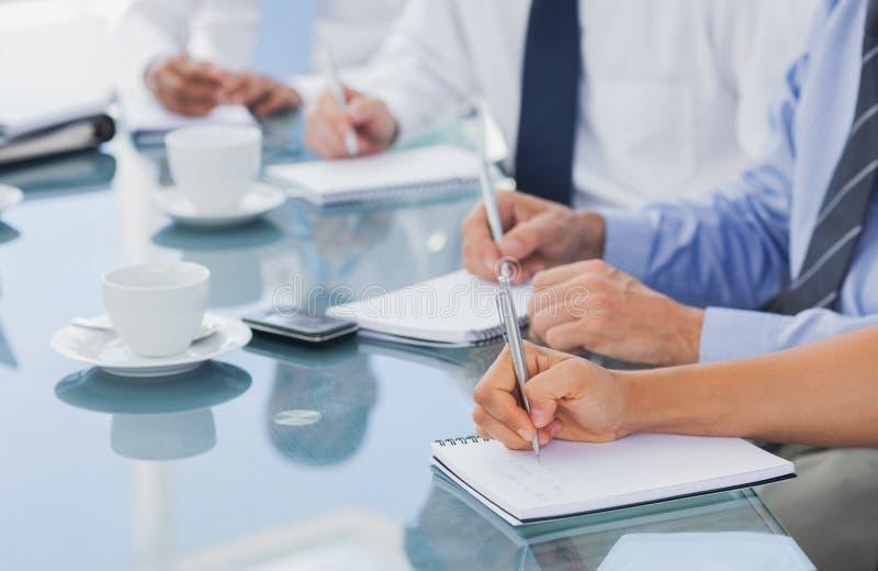Händer för affärsfolk som tar några anmärkningar royaltyfria foton
