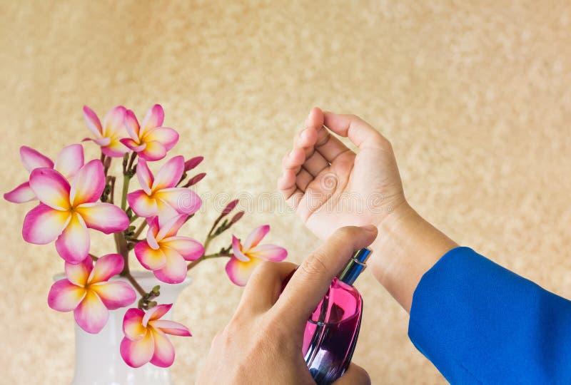 Händer för affärskvinnor som besprutar eller applicerar eller bär doft royaltyfri fotografi