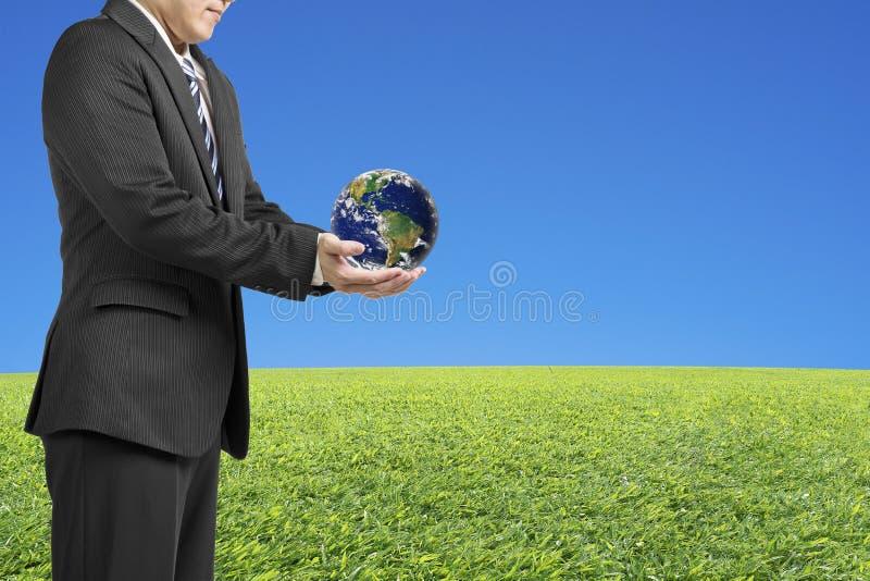 Händer för affärsman två rymmer bollen med den globala översikten med ny gräsplan royaltyfri bild