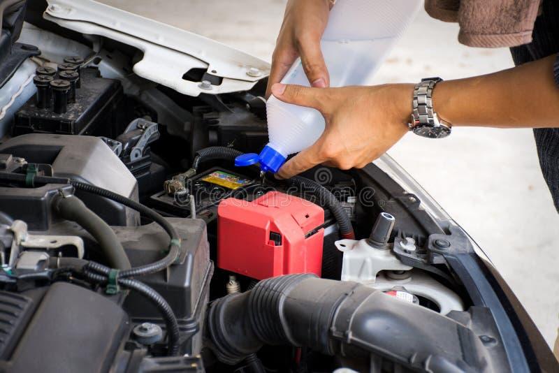 Händer för arbetare för för man eller automatisk mekaniker tillfogar destillerat vatten till bilbatteriet Kontrollera och underhå royaltyfri foto