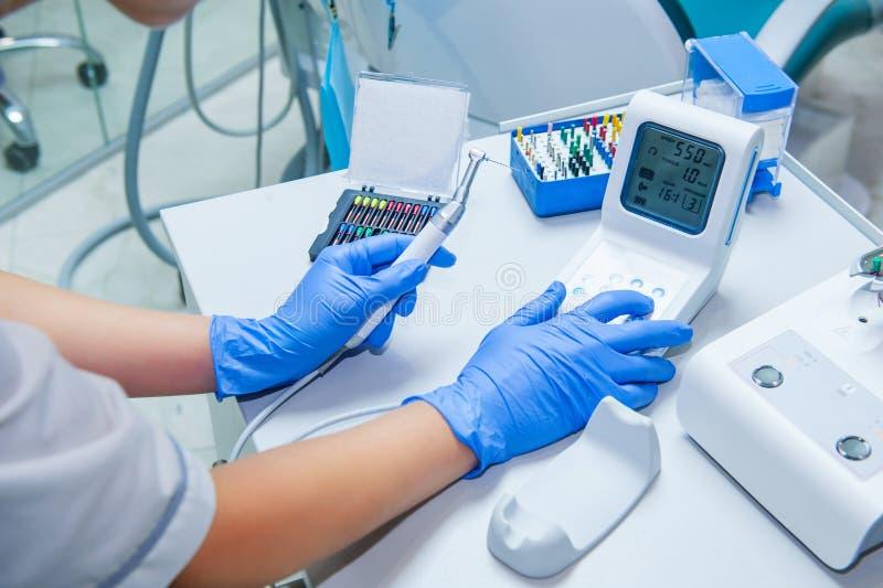 Händer för assistent` s konfigurerar tand- utrustning i kontor för tandläkare` s Nära övre, selektivt fokuserar dentistry royaltyfri bild