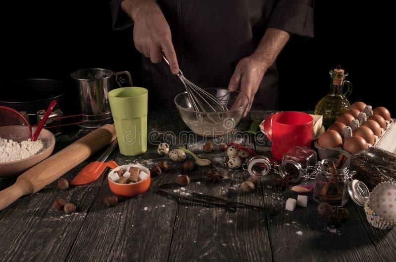 Händer för bagare` s piskade med viftar vaktelägg i bunken som isolerades på svart arkivfoton